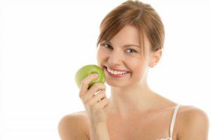 En ung dame der spiser sundt for at undgå tandkødsbetændelse